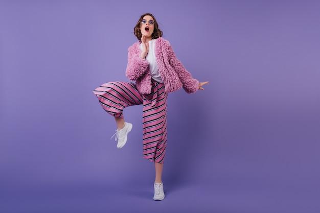 Ragazza allegra europea divertente in scarpe da ginnastica bianche che posano sulla parete viola. debonair giovane donna in pantaloni a righe ballando.
