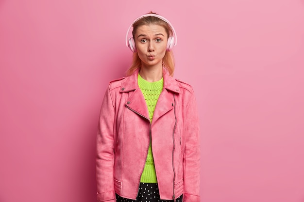 Funny european girl keeps lips rounded, listens music in headphones, picks song in playlist, being on her way to school, dressed in fasionable pink jacket, enjoys favorite singer