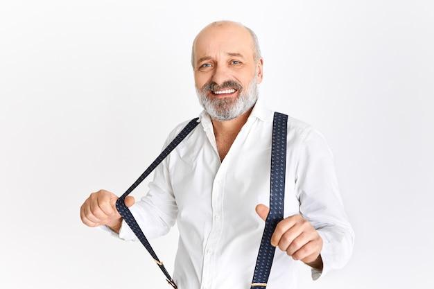 대머리 머리와 회색 수염을 가진 재미있는 유럽 남성 연금 수령자 우아한 흰색 셔츠를 입고 격리 된 포즈, 멜빵 조정, 저녁 식사