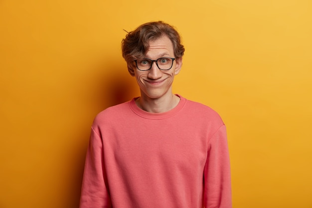 Funny european man has pleased expression, smiles joyfully, wears optical glasses and rosy jumper, hears good news, isolated over yellow wall, express good emotions. male nerd in spectacles
