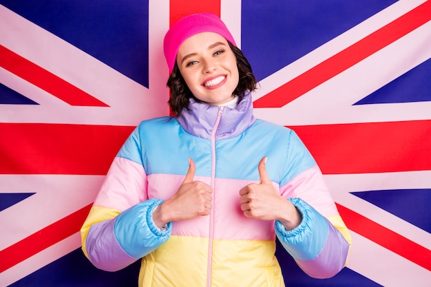 Funny exchange student lady making abroad photos for parents wear warm colored coat isolated pink background