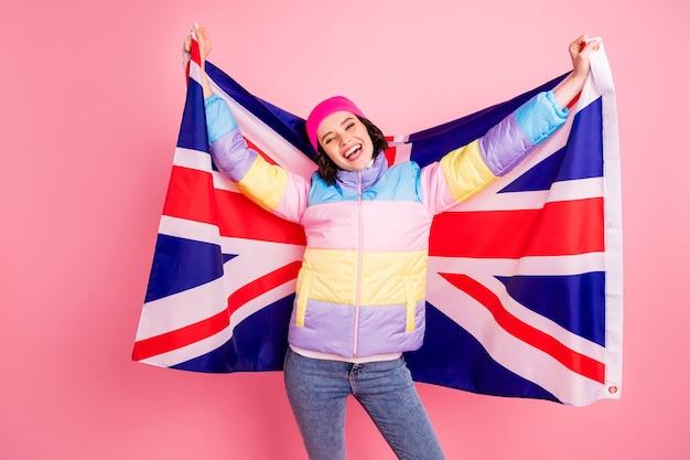 플래그와 함께 사진을 만드는 재미 교환 학생 아가씨 따뜻한 컬러 코트 절연 분홍색 배경을 착용