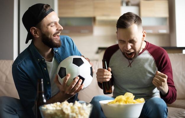 집에서 소파에 앉아있는 동안 tv에서 축구를보고있는 간식과 맥주와 함께 재미있는 흥분된 hipster 수염 친구. 팀 승리로 외치는 팬들