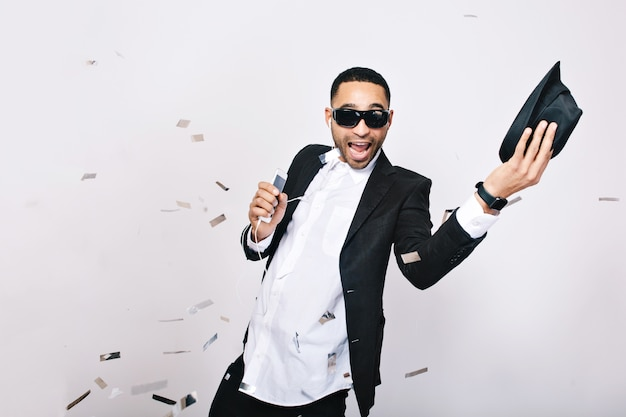 Funny excited young man in suit having great party celebration time in tinsels. wearing black sunglasses, smiling, singing, listening to music, expressing positivity.