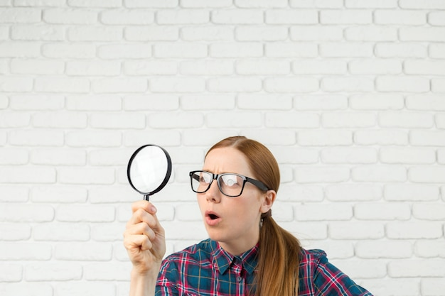 Funny expression, shocked woman looking through a magnifying glass,