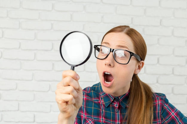 Funny expression. shocked woman looking through a magnifying glass.