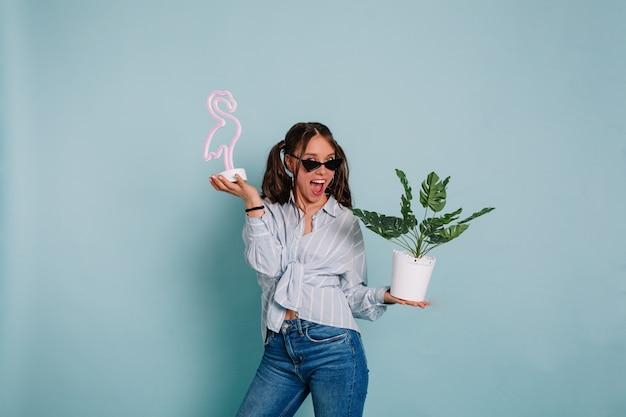 青いシャツとジーンズを着て、青い壁にピンクのフラミンゴと植木鉢を持って素晴らしい笑顔でポーズをとって黒髪の面白い表現力豊かな若い女性