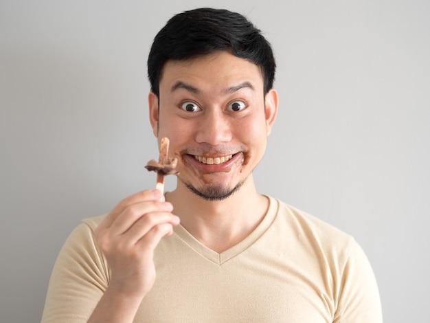 面白い顔アジア人はチョコレートのバニラアイスポップを食べる。