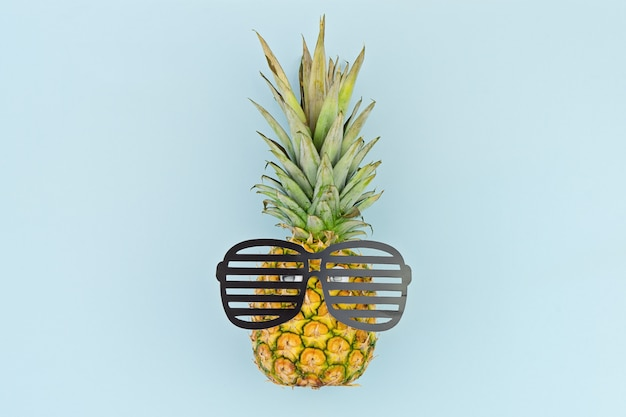 Funny face by pineapple with glasses on blue
