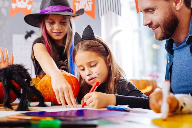 Funny face. cute little girl wearing cat halloween costume having funny painted face while coloring pictures
