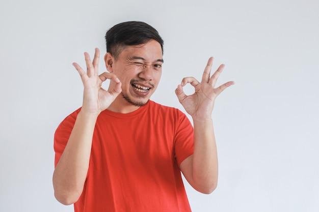 両手にウインクとokジェスチャーで赤いtシャツを着ているアジア人男性の変な表情