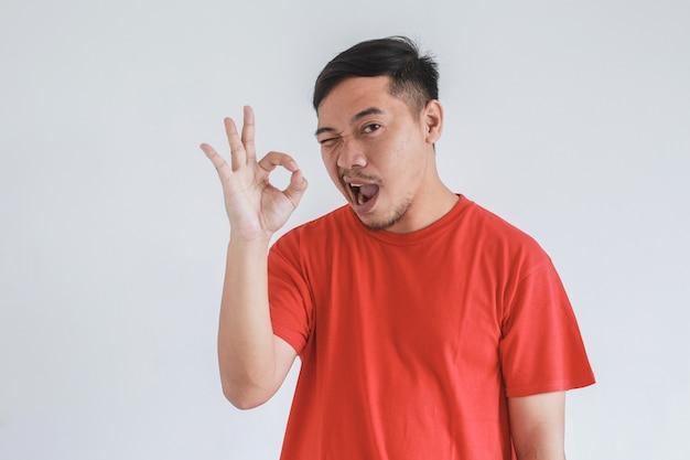 ウィンクとokジェスチャーを手に赤いtシャツを着ているアジア人男性の変な表情
