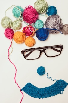 Funny face made of multicolored clews and glasses on white background.