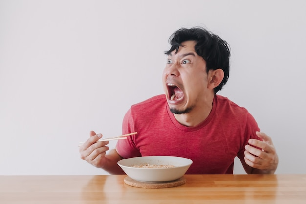 Funny face of man eat very hot and spicy instant noodle