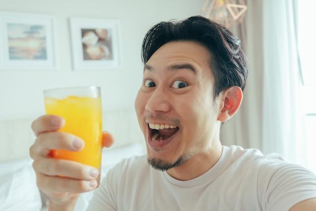 男の変な顔は夏休みのためにホテルで新鮮なオレンジジュースを飲みます