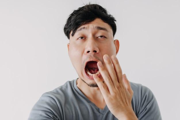 白い背景で隔離のあくびをする男の変な顔