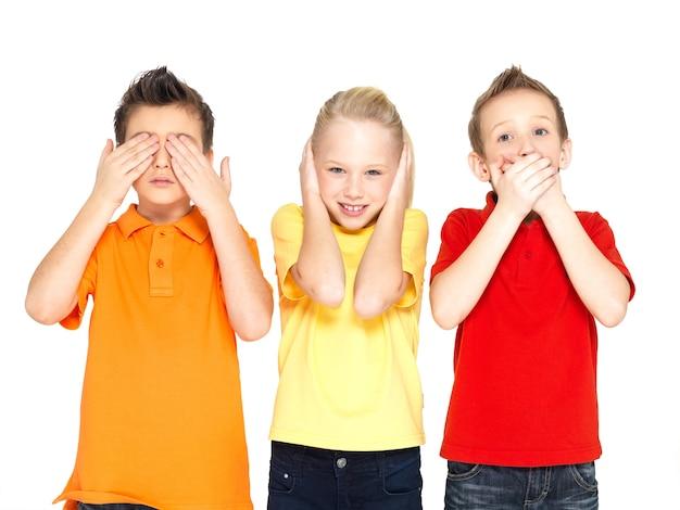 Смешные лица счастливых детей, делающих «ничего не вижу, ничего не слышу, ничего не говори ...», изолированные на белом фоне
