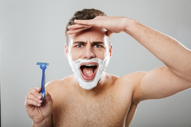Funny facial expressions of unshaved male doing morning procedure with razor and cream on face over grey wall