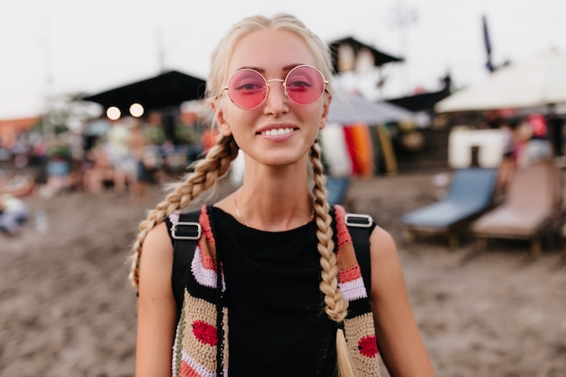 Donna bionda divertente con le trecce che posano sul fondo della spiaggia della sfuocatura. outdoor ritratto di spensierata donna bionda in abbigliamento alla moda indossa occhiali da sole rosa.