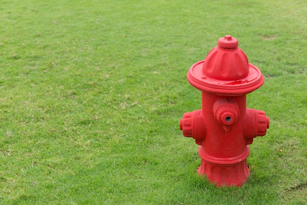 Funny fake red fire hydrant on green grass field of kid park