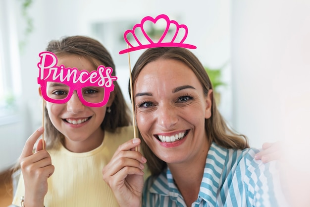 Funny family on a background of bright wall. mother and her daughter girl with a paper accessories. mom and child are holding paper crown on stick.