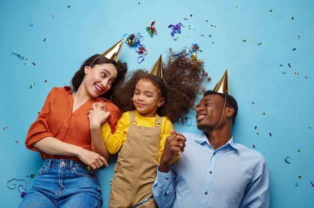 Funny family in caps celebrate birthday, blue background. pretty little girl and her parents, event celebration, balloons and confetti decoration