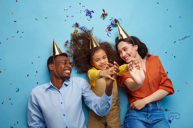 Funny family in caps celebrate birthday. pretty little girl and her parents, event celebration, balloons and confetti decoration