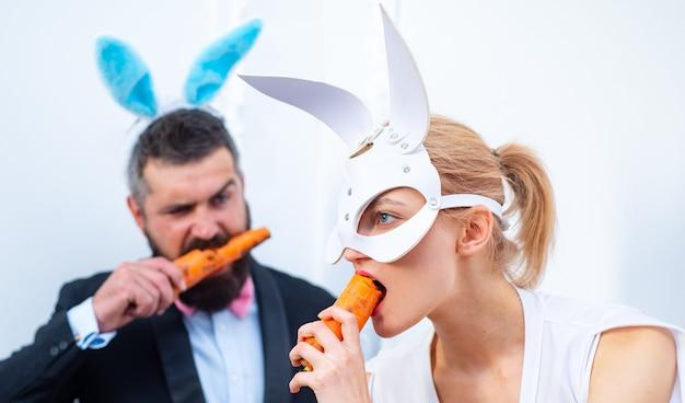 재미있는 가족은 부활절을 축하합니다. 부활절 토끼. 토끼 커플. 즐거운 휴일 보내세요. 토끼 귀를 가진 부부는 당근을 먹고 있습니다.