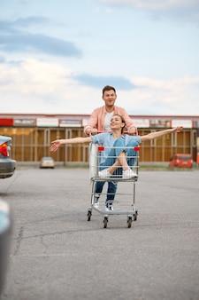 Смешная семейная пара едет в тележке на автостоянке супермаркета. счастливые клиенты, несущие покупки из торгового центра, автомобили на заднем плане, мужчина и женщина на рынке