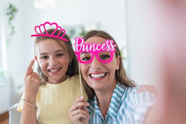 明るい壁を背景に面白い家族。紙のアクセサリーを持つ母と娘の女の子。ママと子供はスティックに紙の王冠を持っています。