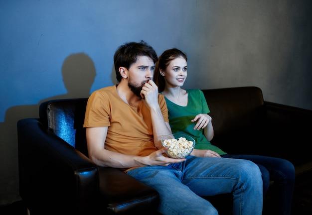 Смешная семья сидит дома на диване, смотрит фильмы попкорн эмоции. фото высокого качества