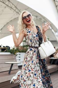 ストリートでファッショナブルな白いバッグとパターンのスタイリッシュなドレスでサングラスをかけた面白いファッションの美しい流行に敏感な女性
