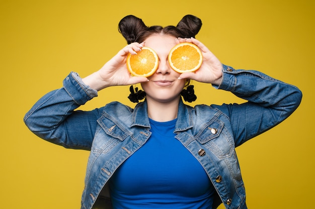 Funny fashionable girl with hairstyle holding oranges on eyes.