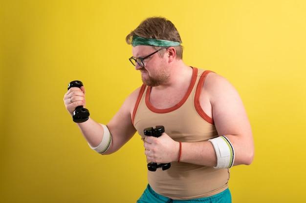 아령으로 운동을 하 고 재미있는 뚱뚱한 남자. 초과 중량. 노란색 배경입니다.