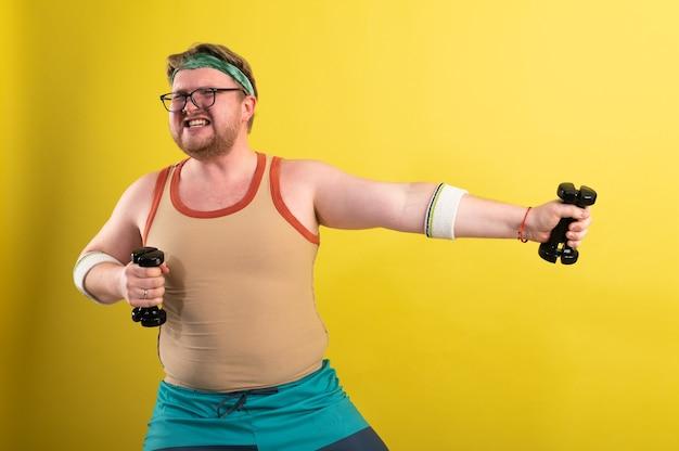 Забавный толстяк делает упражнения с гантелями. избыточный вес. желтый