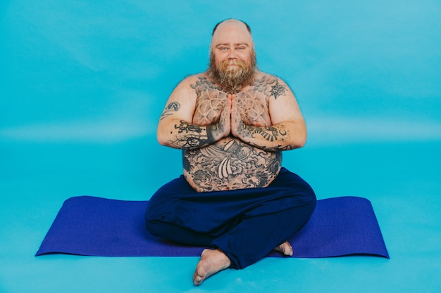 ヨガ瞑想をしている面白い太った男面白いと皮肉なキャラクター