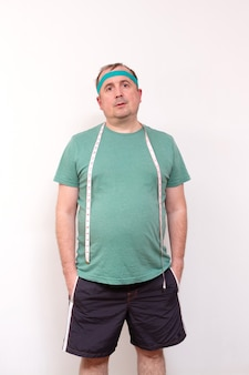 A funny fat man in a green bandana and a t shirt with a measuring tape around his neck home fitness training independent training