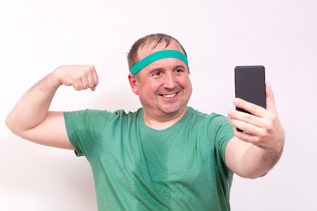 A funny fat man in a green bandana and t shirts takes a selfie of his right bicep home fitness training independent distance learning