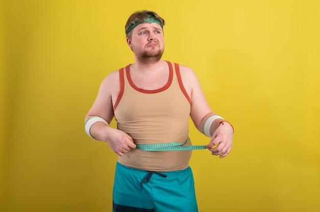 Забавный толстый мужчина в спортивной одежде измеряет объем тела.