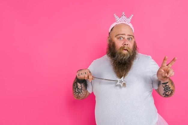 ピンクの壁にチュチュを持ったバレリーナのふりをしている面白い太った男