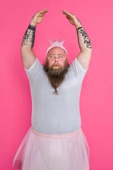 Забавный толстяк притворяется балериной с балетной пачкой на розовой стене