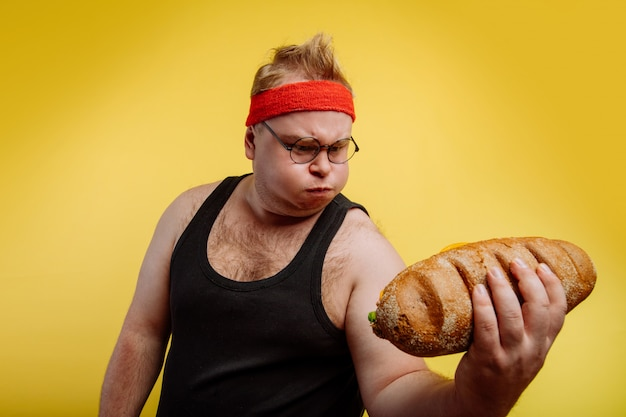 Забавный толстяк потеет, поднимая бургер