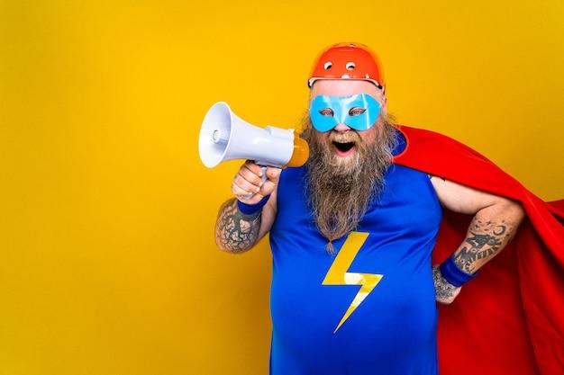 Забавный толстый мужчина в костюме супергероя, выступающий в роли сверхчеловека с особыми способностями, портрет на цветной стене
