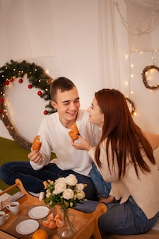 Смешно кормить друг друга. позирует для моделей на рождество. семейный ужин в новогоднюю ночь, завтрак в постель