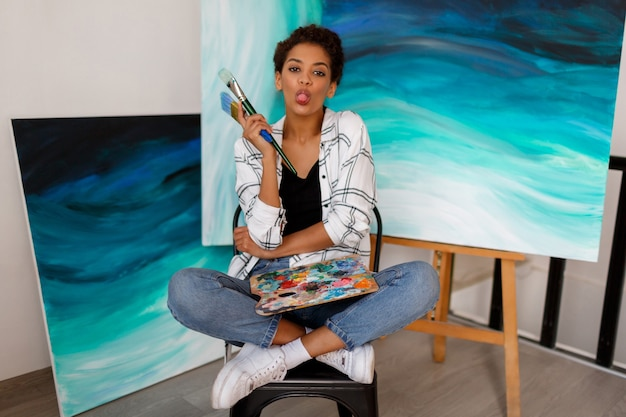 Funny female artist sitting with amazing abstract sea acrylic hand drawn artwork. holding brushes and palette