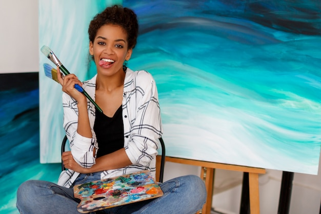 Funny female artist  sitting with amazing abstract sea acrylic hand drawn artwork at the studio. holding brushes and palette.