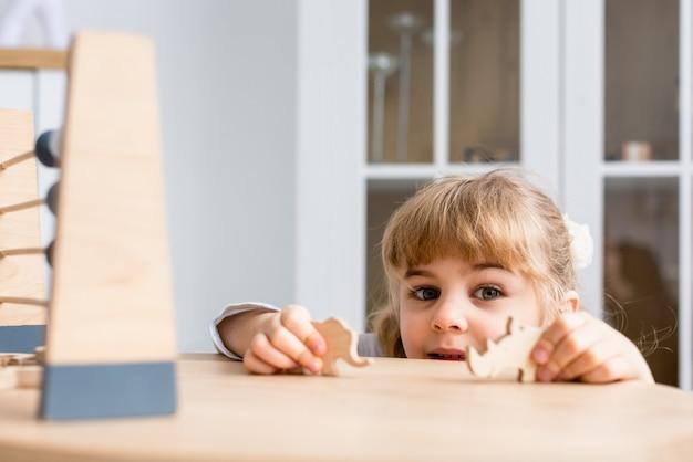 面白い女性の赤ちゃんは、木の動物とスコアで家で遊ぶ