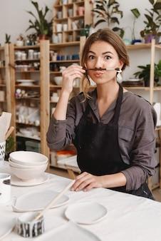 Funny female ceramist in pottery studio.
