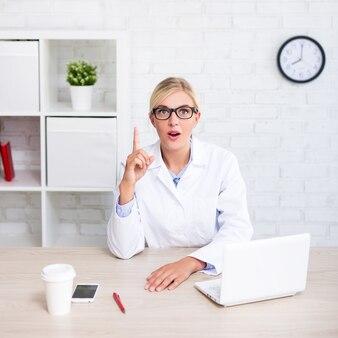 現代のオフィスでアイデアサインを示す面白い女性医師または科学者