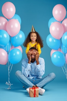 Funny female kid congratulates her father, blue background. pretty child hugs her dad, event or birthday party celebration, balloons and gift box decoration